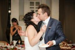 Braut zieht dem Bräutigam eine Hochzeitstorte ein Lizenzfreies Stockbild