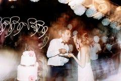Braut zieht einen Bräutigam mit einer Hochzeitstorte ein stockfotografie