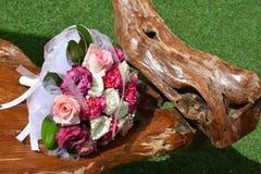 Brautblumenstrauß auf einem Holzstuhl auf dem grünen Gras Lizenzfreies Stockfoto