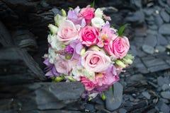 Brautblumenstrauß auf schwarzen Steinen Lizenzfreies Stockfoto