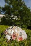 Brautblumenstrauß, der auf dem Grün liegt Stockfotografie