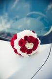 Brautblumenstrauß, der auf der Haube eines Autos liegt Stockfoto