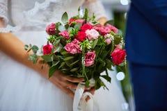 Brautblumenstrauß der Rosennahaufnahme in den Händen die Braut lizenzfreie stockbilder