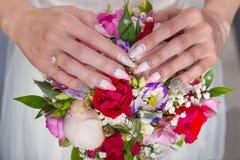 Brautblumenstrauß der schönen Hochzeit von Rosen und von Pfingstrose mit ihren Händen auf dem Blumenstrauß, lange Acrylnägel mit  Stockfoto