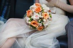 Brautblumenstrauß mit den Rosen, die auf Knien der Braut liegen lizenzfreies stockbild