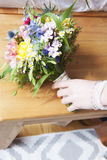 Brautblumenstrauß mit der Hand einer Braut Lizenzfreie Stockfotos