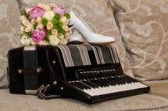 Brautblumenstrauß, Schuhe und Ringe auf Akkordeon stockbilder