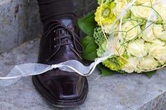 Brautblumenstrauß- und Bräutigamschuh Stockbild