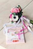 Brautblumenstrauß und Einladung auf einer Hochzeit Lizenzfreie Stockfotografie