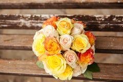 Brautblumenstrauß und Ringe auf der Bank Stockfoto