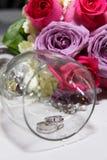 Brautblumenstrauß und -ringe im Glas Stockfotos