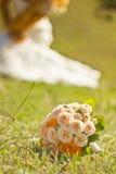 Brautblumenstrauß und weißes Hochzeitskleid an Lizenzfreie Stockfotos