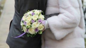 Brautblumenstrauß von gelben und purpurroten Rosen in der Hand einer Braut stock video footage