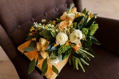 Brautblumenstrauß von Sahnerosen und von weißen Pfingstrosen in einer rustikalen Art im braunen Stuhl Lizenzfreie Stockbilder