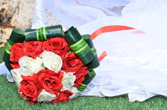 Brautblumenstrauß von Scharlachrot- und weißenrosen mit grünen Blättern auf dem Rand eines Hochzeitskleides Lizenzfreie Stockfotografie