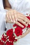 Brautbräutigam-Hochzeits-Hände auf Blumenstrauß Stockfotos