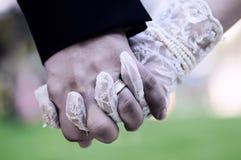 Brautbräutigamhand, die an grünen Hintergrund hält Lizenzfreie Stockbilder