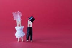 Brautbräutigamhochzeitseinladungs-Kartenschablone Wäscheklammercharaktere in der Liebe Rosa violetter Papierhintergrundkopienraum Lizenzfreie Stockfotos