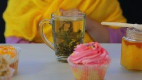 Braute frisch grünen Tee in einer transparenten Schale auf einer grauen Tabelle mit Kuchen stock footage