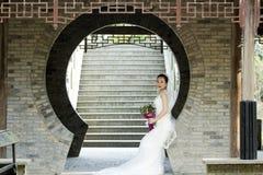 Brautgriff-Brautblumenstrauß mit weißem Hochzeitskleid nahe einem Ziegelsteinbogen Stockfoto