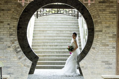Brautgriff-Brautblumenstrauß mit weißem Hochzeitskleid nahe einem Ziegelsteinbogen Lizenzfreies Stockfoto