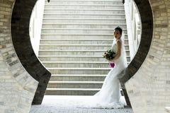 Brautgriff-Brautblumenstrauß mit weißem Hochzeitskleid nahe einem Ziegelsteinbogen Stockfotos