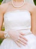 Brauthände mit Ring über dem Hochzeitskleid Lizenzfreie Stockbilder