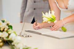 Brauthand mit einer unterzeichnenden Hochzeitslizenz des Stiftes Ehevertrag Lizenzfreies Stockfoto