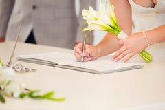 Brauthand mit einer unterzeichnenden Hochzeitslizenz des Stiftes Ehevertrag Lizenzfreies Stockbild