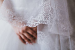 Brauthände auf weißem Kleid, bereiten für Trauung vor und warten Stockbild