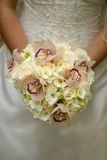 Brautholding ihr Hochzeitsblumenstrauß Lizenzfreie Stockfotos