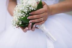 Brautholding ihr Hochzeitsblumenstrauß lizenzfreie stockbilder