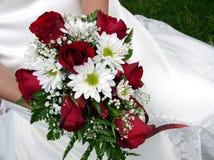 Brautholding ihr Hochzeitsblumenstrauß gegen ihr Kleid Lizenzfreie Stockfotos