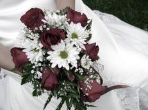 Brautholding ihr Hochzeitsblumenstrauß gegen ihr Kleid Stockfoto