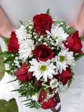Brautholding ihr Hochzeitsblumenstrauß gegen ihr Kleid Lizenzfreies Stockfoto