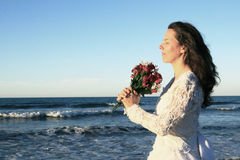 Brautholdingblumenstrauß durch Ozean stockbild