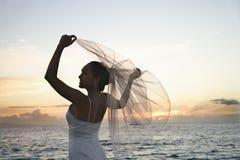 Brautholdingschleier auf Strand stockfotografie