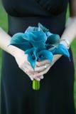 Brautjunfer, die blauen Blumenstrauß anhält Lizenzfreies Stockfoto