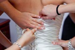 Brautjunfern, die beim Kleid helfen lizenzfreies stockfoto