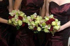 Brautjunfern, die ihre Hochzeitsblumensträuße anhalten stockfoto