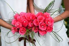 Brautjunfern mit vibrierenden rosafarbenen Blumensträußen Lizenzfreies Stockfoto