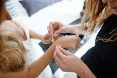 Brautjungfer hilft, ein Armband auf seinen Arm für die Braut zu setzen stockfotografie
