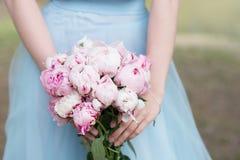 Brautjungfer im blauen Kleidergriffblumenstrauß mit weißer und rosa Pfingstrose Stockbilder