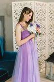 Brautjungfer im purpurroten rosa Hochzeitskleid und Haarrebe winden Kristallbergkristallkrone tsmiles und betrachten Blumenstrauß lizenzfreies stockfoto