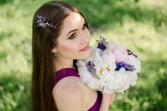 Brautjungfer mit luxuriösem buntem Hochzeitsblumenstrauß von den Pfingstrosen und von anderen Blumen, die an der Zeremonie im Pur Stockfotografie