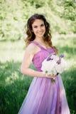 Brautjungfer mit luxuriösem buntem Hochzeitsblumenstrauß von den Pfingstrosen und von anderen Blumen, die an der Zeremonie stehen stockfotos
