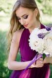 Brautjungfer mit luxuriösem buntem Hochzeitsblumenstrauß von Pfingstrosen und von anderen Blumen mit dem Berufsmake-up, das an st lizenzfreie stockfotografie