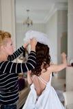 Brautjungfer schnürt sich weißes Hochzeitskleid für schöne Braut Stockfoto