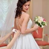 Brautjungfer schnürt sich weißes Hochzeitskleid für schöne Braut Stockfotos