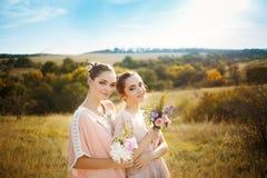 Brautjungfern in den rosa Kleidern mit Blumensträußen stockbild